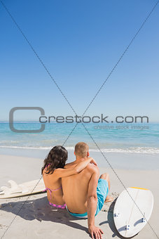 Cute young couple sitting with their surfboards