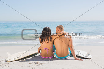 Pretty young couple sitting with their surfboards