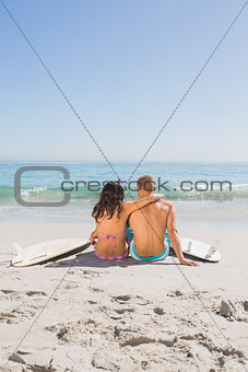 Beautiful young couple sitting with their surfboards