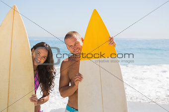 Cute young couple holding their surfboards