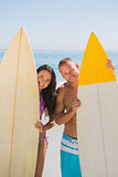 Smiling young couple holding their surfboards