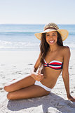 Sexy young tanned woman wearing straw hat posing