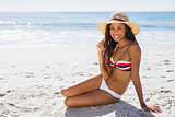 Smiling young tanned woman wearing straw hat posing