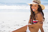 Cheerful young tanned woman wearing straw hat posing