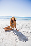 Happy young tanned woman wearing straw hat posing