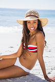 Happy young tanned woman wearing straw hat relaxing