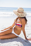 Young tanned woman wearing straw hat relaxing