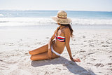 Young sexy woman wearing straw hat taking sun