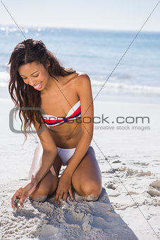 Happy young sexy woman touching sand