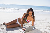 Sexy young woman in bikini using her laptop
