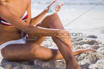 Woman applying sun cream on her leg
