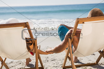 Cute couple holding hands while lying on their deck chairs