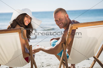 Cute couple looking at camera while lying on their deck chairs