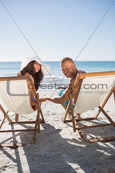 Cute couple smiling at camera while lying on their deck chairs