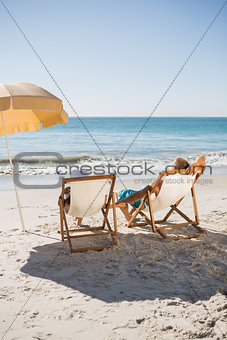 Happy couple sunbathing on their deck chairs