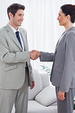 Happy colleagues shaking hands during meeting