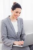 Busineswoman using laptop sitting on sofa