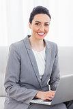 Smiling busineswoman using laptop sitting on sofa