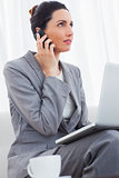 Businesswoman calling with her mobile phone and using laptop sitting on sofa