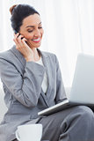 Smiling businesswoman calling with her mobile phone and using laptop sitting on sofa