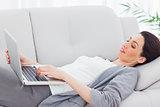 Smiling businesswoman lying on sofa using laptop