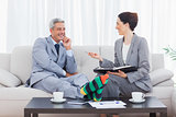 Funny businessman wearing stripey socks and laughing with his colleague