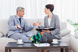 Funny businessman wearing stripey socks and talking with his colleague