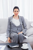 Outraged businesswoman sitting on sofa looking at camera