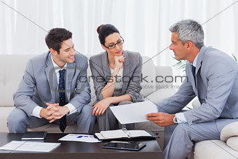 Business people working and talking together on sofa