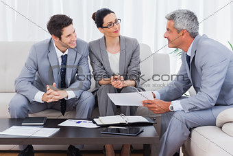 Smiling business people working and talking together on sofa
