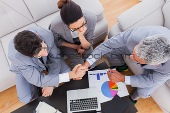 Business people sitting on sofa shaking hands during meeting