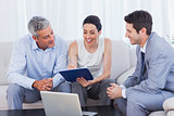 Woman signing contract as husband and salesman watch