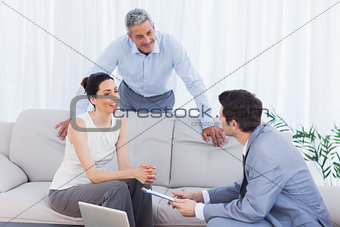 Salesman talking with customers on couch