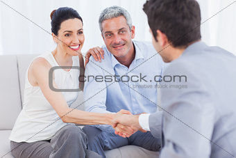 Woman shaking hands with salesman sitting beside husband