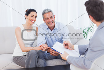 Couple listening to salesman holding contract