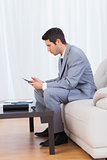 Businessman sitting on sofa texting message with his mobile