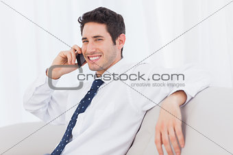 Businessman calling with his mobile phone on sofa