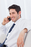 Smiling businessman calling with his mobile phone on sofa