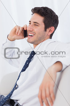 Happy businessman calling with his mobile phone on sofa