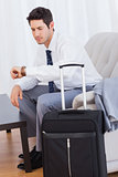 Businessman with his baggage waiting for flight sitting on sofa