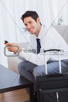 Happy businessman with suitcase and mobile phone