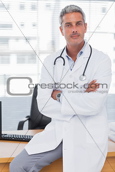 Serious doctor sitting on desk with arms crossed