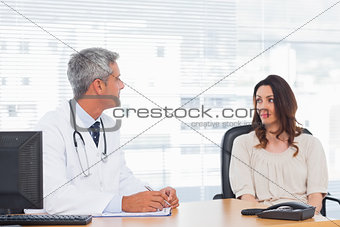 Doctor talking with his patient and writing on notebook