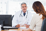 Doctor listening to his patient talking about her illness