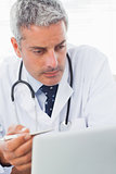 Concentrated doctor watching something on his laptop