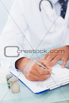 Hand of a doctor writing on a prescription pad