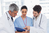 Nurse and doctors looking together a file