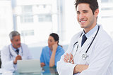 Happy doctor looking at camera with colleagues behind