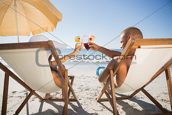 Happy couple clinking their glasses while relaxing on their deck chairs