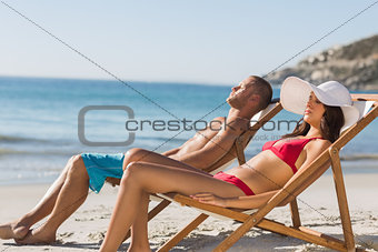 Young couple sleeping on their deck chairs